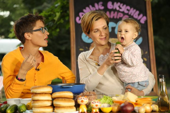 """Albina Preis with her daughter Rona in her arms while recording one of the shows. Photo: Facebook """"Two and a half cooks"""""""