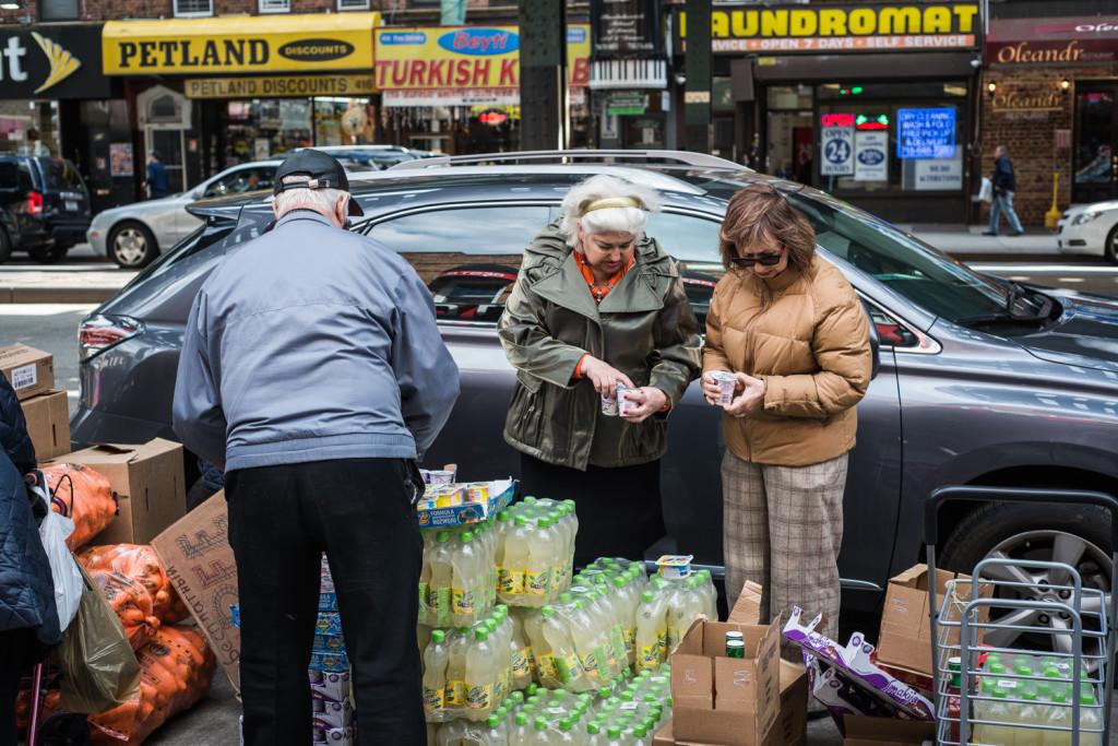 Жители Брайтон Бич выбирают бесплатные продукты, срок годности которых вот-вот закончится. Фото Павел Терехов